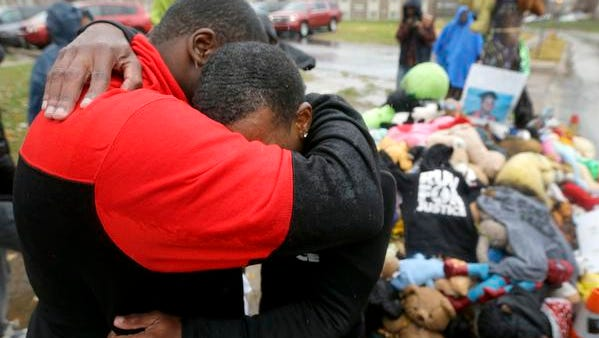 Local resident Tory Russell, left, comforts Londrelle Hall after Hall and another man ran from their home in Atlanta to a memorial in the middle of a street Sunday, Nov. 23, 2014, more than three months after a black 18-year-old was shot and killed there by a white policeman in Ferguson, Mo.  It took Hall 20 days to make the run which he did to raise awareness of the shooting. Ferguson and the St. Louis region are on edge in anticipation of the announcement by a grand jury whether to criminally charge Officer Darren Wilson in the killing of Michael Brown.