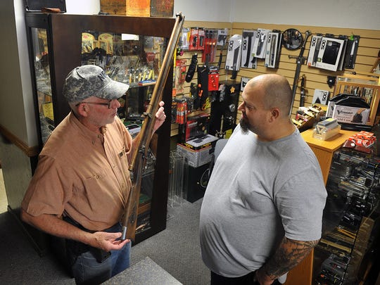 Jim Lawrence, left, manager of the accessories shop of Texas Knifeworks and Guns, talks with Brent Barcus about a 50 cal. muzzle-loading replica buffalo gun. The store buys, sells and trades pistols, rifles and shotguns and offers a full selection of accessories, cleaning supplies, reloading equipment and knives.