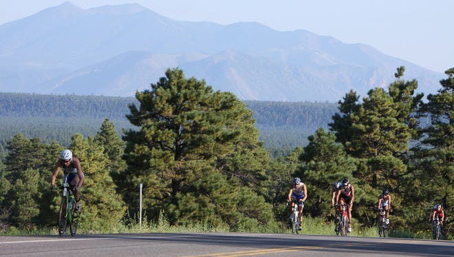 Triathletes at the Mountain Man Triathlon race down Lake Mary Road near Flagstaff. The Arizona high country offers a lot of options for outdoor activities and an escape from the Valley's summer heat.