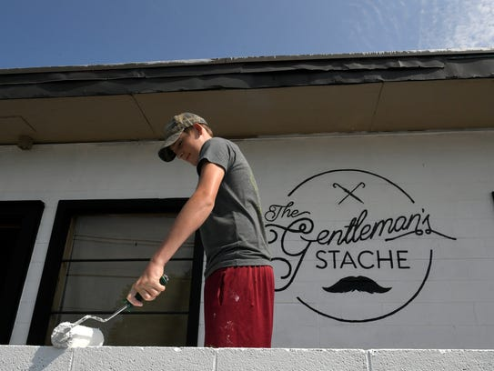 Luke Stahl paints a wall for a new store opening in