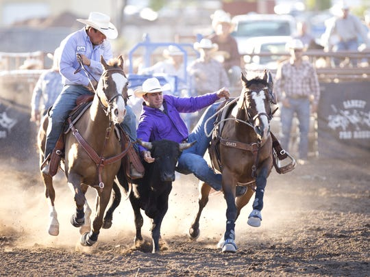 Bridger Chambers, right, tackles a steer during the