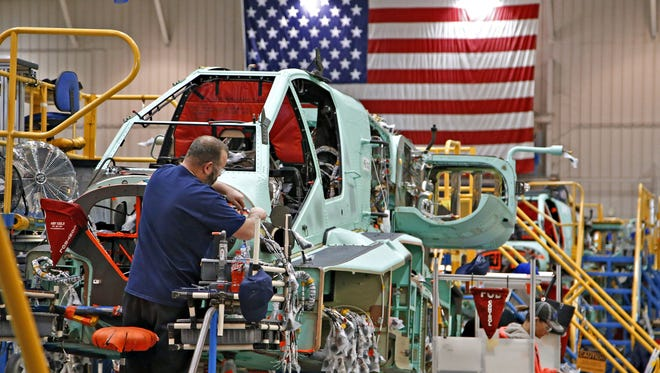 An electrical technician works on the wiring harness in the nose cone of an AH-64E Apache attack helicopter on the assembly floor at the Boeing manufacturing facility in Mesa on March 9, 2016.