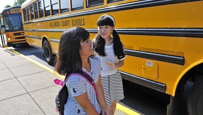Michika Oikawa, 14, right, and Nei Mizota, 12, English Language Learners (ELL) students, who are from Japan, walk to an awaiting school bus during an orientation at Walnut Grove Elementary School in Franklin, Tenn., Tuesday, July 28, 2015.