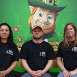 Green Emerald Restaurant and Pub co-owner Cheryl McIntyre, pictured right, sits in front of the Bellevue restaurant's lucky leprechaun Monday with staff members Dustin Vickery and Jenny Galloway. The restaurant is located at 137 E. Main St.