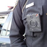 The Taser Axon Flex camera, as seen here, can be worn on the collar or clipped to other parts of the uniform or sunglasses. The VIEVU camera can be clipped to part of the uniform or mounted in the vehicle.