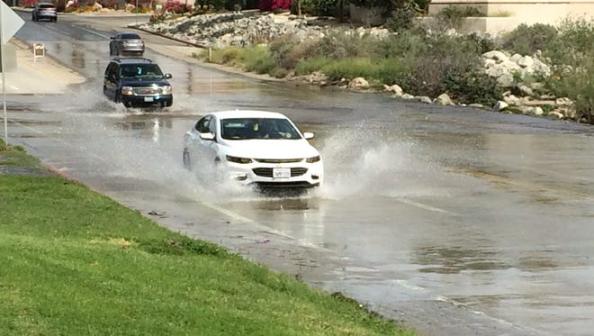 Traffic passes through a flooded Cathedral Canyon Drive Wednesday morning. Water continues to flow through the Whitewater Wash even though there hasn't been rain for nearly a month.
