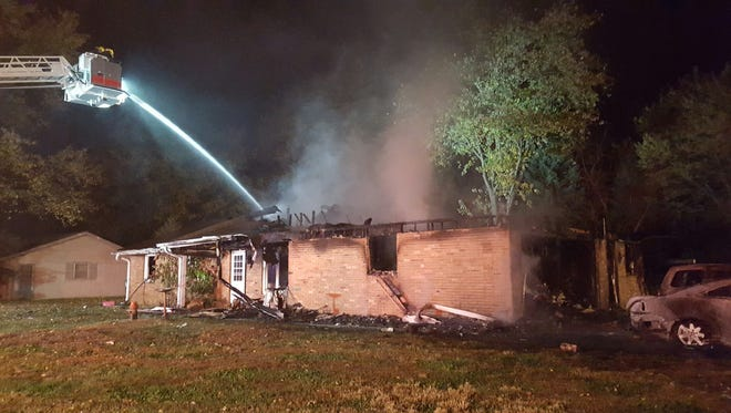 Firefighters work at a residential fire at 3101 N. Country View Drive early Friday morning.