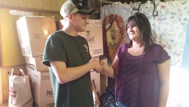Fannett-Metal High School senior Chase Hartman, left, shakes hands with Valley Ministries manager Cindy Erwin after donating several bags and boxes worth of clothes recently to the group as part of his senior project.