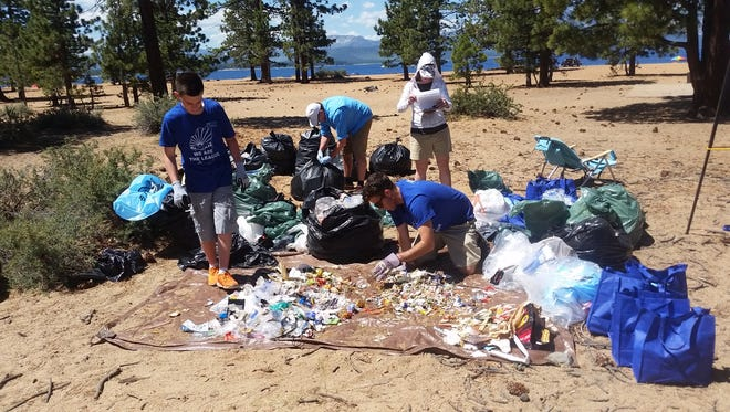 Volunteers clean trash from Nevada Beach at Lake Tahoe following the Fourth of July holiday in 2015.