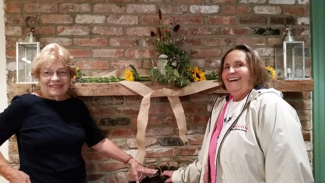 Rose Ullrich and Stephanie Karoly at the mantle with floral arrangement