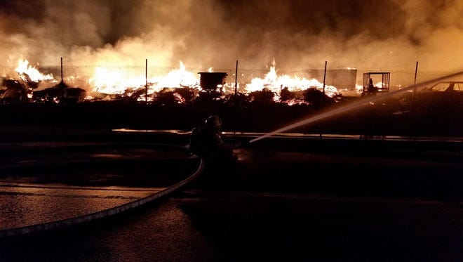 Firefighters battle a three-alarm blaze at a pallet yard in Perris early Friday morning, Nov. 18, 2016.