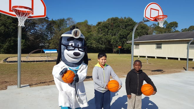 UnitedHealthcare mascot, Dr. Health E. Hound with Herod Elementary students on their new outdoor basketball court.