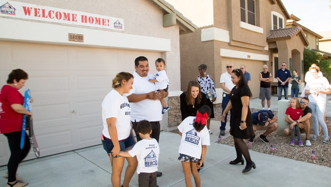 retired Army Specialist Alexis Jacquez Gamez and his family receive a warm welcome home from JPMorgan Chase Bank Senior Vice President and Regional Director Heather Ellison. Chase and non-profit Building Homes for Heroes donated a mortgage-free home in Sun City on March 21, 2017, to the Gamez family.