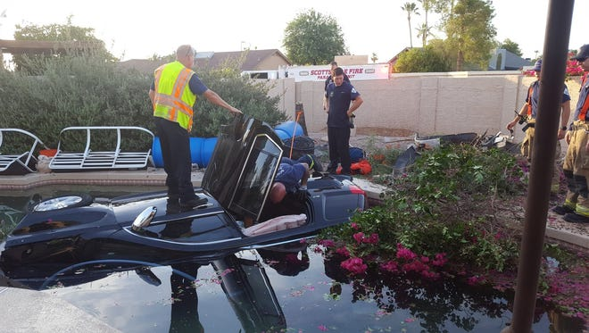 Scottsdale firefighters rescued an elderly motorist from a car that plunged into a backyard pool Monday