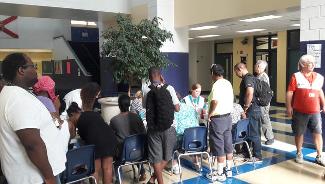Residents up to register with volunteers and county workers to wait out Hurricane Irma at Varsity Lakes Middle School in Lehigh Acres. Shelter managers say there was already a line when the facility opened Friday morning at 9 a.m.