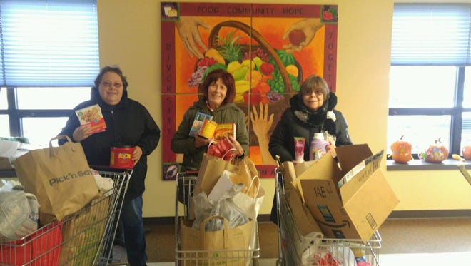 """Salvation Army is grateful for the outpouring of help from individuals and groups who re-supply hygiene and shower items, laundry soap and meals.The 2017 Red Kettle Campaign will help fund warming shelter staff and facility upkeep. Pictured are Green Garden Club  members Sandy Smet, Dorothy Wollersheim and Charlotte Nelson. Green Thumb Garden Club members chose the warming shelter as their community project and donated three shopping carts of warming shelter supplies to live their motto: """"Coming together is a beginning, keeping together is progress, and working together is success."""""""