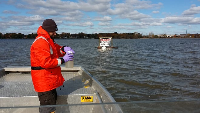 U.S. Fish and Wildlife Service employee Anthony Rieth holds a 2-liter water sample collected from the Lower Fox River.