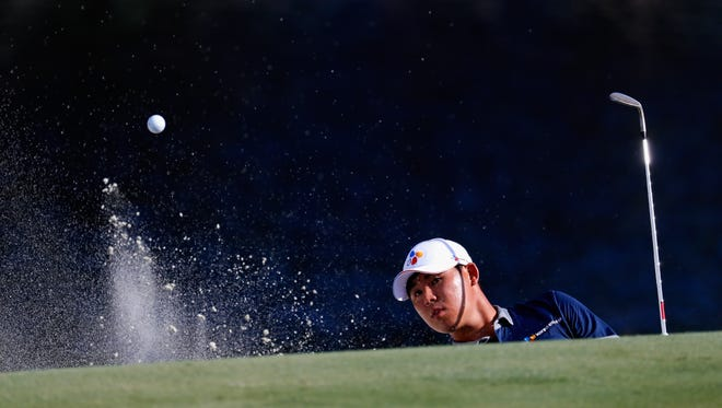 Si Woo Kim hits a shot from the sand on the 15th hole during the third round of the Wyndham Championship Saturday at Sedgefield Country Club.
