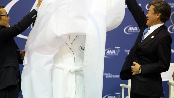 A new champion's robe is unveiled by Seiji Kondo of Imabari Towel (left) and All Nippon Airways executive vice president of marketing and sales Takashi Shiki (right) on Tuesday, March 31, 2015 during a press conference at the ANA Inspiration golf tournament in Rancho Mirage, Calif. The robe is presented to the winner after a traditional leap into Poppie's Pond along the 18th green following her win.
