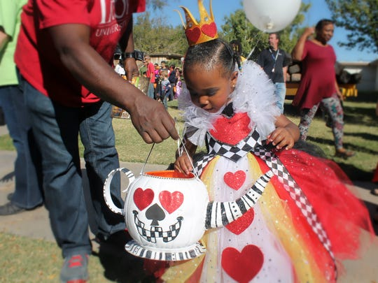 Eva Joy, 2 years old, looks through her candy stash during Zoo Boo on Saturday. Eva was dressed up as the Queen of Hearts.