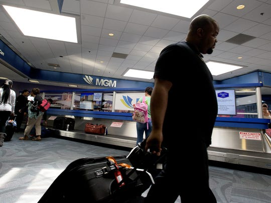Passengers pick up luggage after arriving at the Montgomery