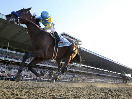Victor Espinoza, aboard American Pharoah, looks back after crossing the finish line to win the Belmont Stakes.