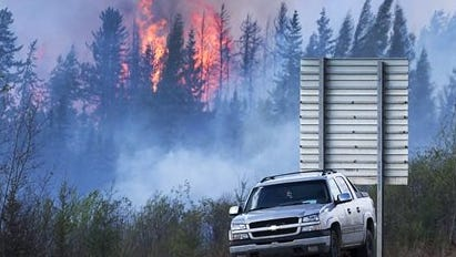 """Flames flare up from hotspots from a wildfire along a highway to Fort McMurray, Alberta, Canada, Sunday, May 8, 2016. Officials said Sunday they reached a turning point in fighting an enormous wildfire, hoping to get a """"death grip'"""" on the blaze that devastated Canada's oil sands town of Fort McMurray amid cooler temperatures and light rain. (Ryan Remiorz/The Canadian Press via AP) MANDATORY CREDIT"""