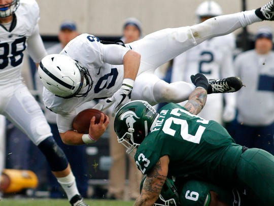Penn State quarterback Trace McSorley, top, is upended