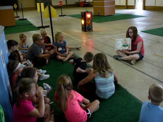 Safety City volunteer Athena Art, 10, reads a story about car safety during the Safety City camp at the Coshocton County Fairgrounds.