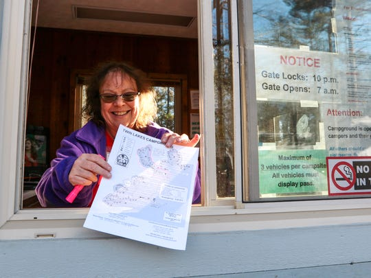Laurie Roebuck, a volunteer, smiles while handing out a map of Twin Lakes campground west of Pendleton. A section of the campground remains open year-round.