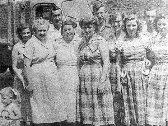 The Stafford family are: from left, front row, Lorene, Edith, Lois, Argie, Bernice, Jo, Lavon; back row, Arlie, Laurel, Keith. Bottom left is baby Kathy (Lorene's daughter). In the background is the Staffords' faithful truck. This picture was taken around 1953.