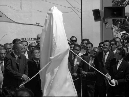 9/25/1964 photo B10, UNVEIL MONUMENT-President Johnson and President Lopez Mateos pull ropes to draw the covering from a special monument marking new boundary agrred to in the Chamizal Treaty. Site is at Bowie High School. Background is billboard size map of Sotuh El Paso area affected by settlement. This was the climax of an impressive ceremony that drew thousands.