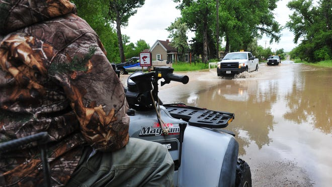 County vehicles drive through flood water on Sun River-Cascade Road in the town of Sun River on Tuesday. The Sun River is expected to crest at 10.1 feet.