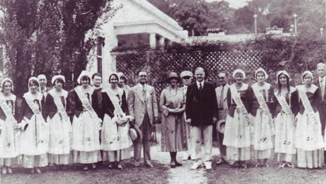 "Louisiana girls in Acadian costume were photographed with former President Herbert Hoover (dark coat, center) in the 1930s during a ""pilgrimage"" to Acadie led by State Sen. Dudley J. LeBlanc (light coat, center)."