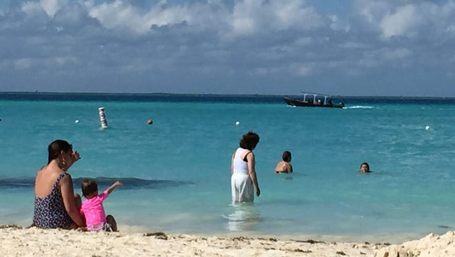 Beaches can be great places to make family memories. Here, a toddler points out a passing boat from the beach at Isla Mujeres, Mexico, in January 2015.