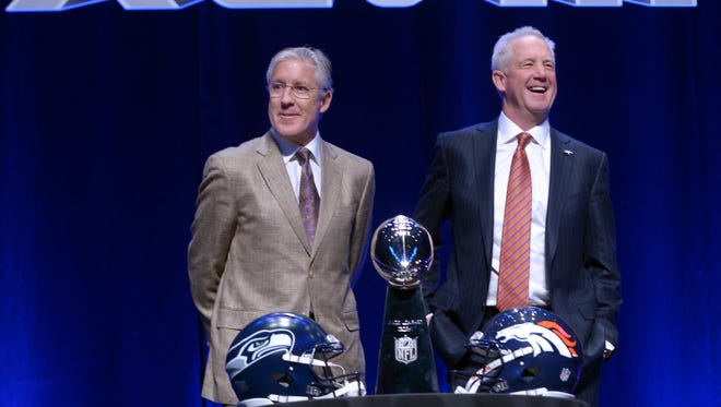 Seattle Seahawks head coach Pete Carroll (left) and Denver Broncos head coach John Fox pose for photos during a Friday press conference at Rose Theater in advance of Super Bowl XLVIII.