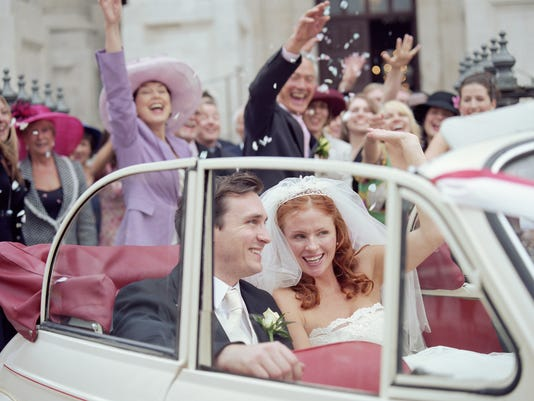 Bride and groom in convertible car, wedding party waving in background