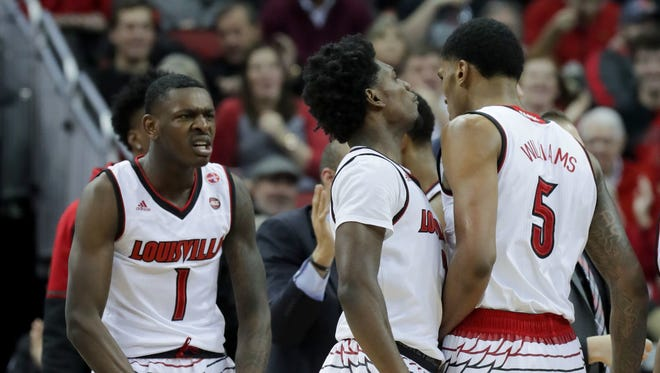 Louisville's Lance Thomas, left, and Darius Perry congratulate teammate Malik Williams after he got the bucket and the foul.