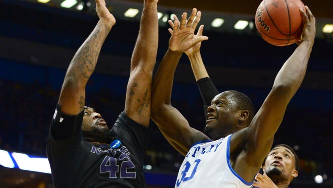 Kentucky Wildcats forward Julius Randle drives to the basket between Kansas State Wildcats forward Thomas Gipson and Shane Southwell in the second half.