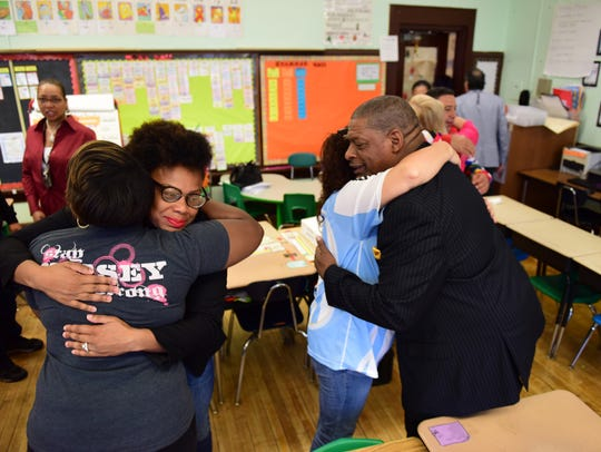 At right, the Rev. Barry Graham, of Canaan Baptist Church, hugs teachers and staff at PS #21 on Friday morning after a prayer service before the school opens.