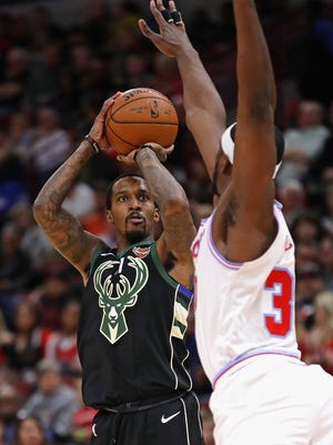 Brandon Jennings of the Bucks focuses on the basket as he gets ready to launch a shot with Noah Vonleh of the Bulls closing in on him Friday night.