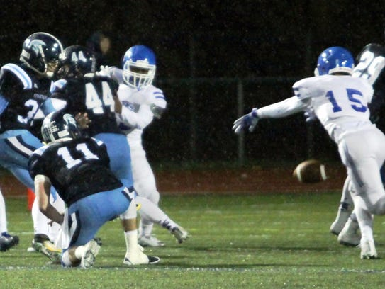 Catholic Central's Jack Downs (15) races after the