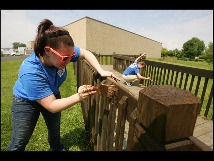 Park National Bank employees Jordann Phillips, left, and Brittany Sharkey, both of Newark, help paint a bridge at LICCO Incorporated Monday afternoon as part of the PNB Cares program.