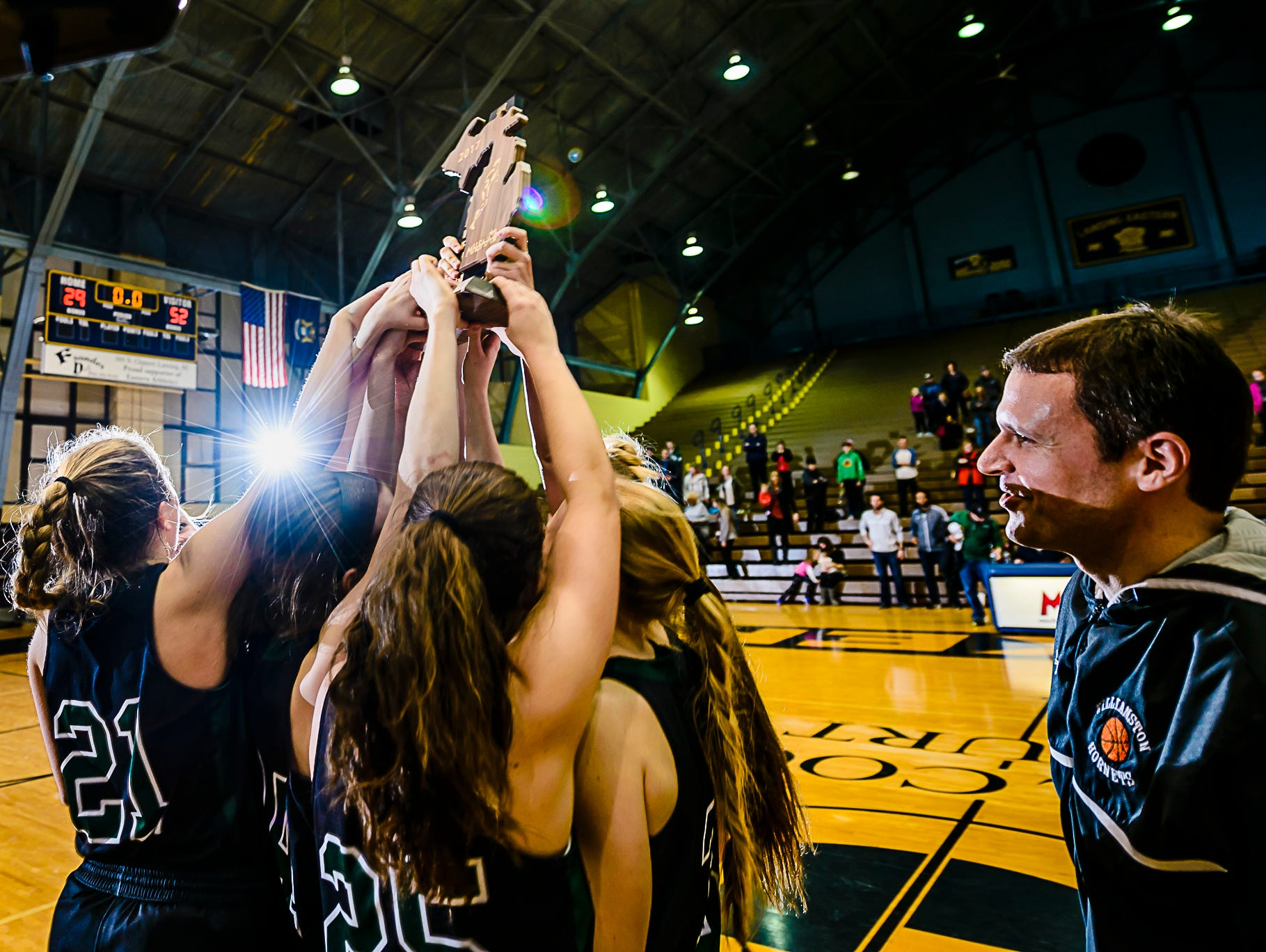 The Williamston girls basketball team lifts the Class B regional championship trophy as head coach Pete Cool ,right, looks on after their win over Portland Thursday March 9, 2017 at Don Johnson Fieldhouse in Lansing. KEVIN W. FOWLER PHOTO