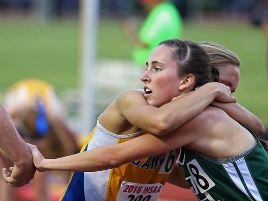 From left, 3200 meter second place finisher, Carmel's Stacy Morozov, hangs from the neck of first place finisher, Pendleton Heights' Alex Buck, at the finish line, during the IHSAA 43rd annual girls track and field state finals, Robert C. Haugh Track and Field Complex at Indiana University, Bloomington, Ind., Friday, June 3, 2016.