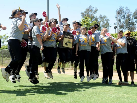 The Newbury Park High softball team jumps for joy while posing with its championship plaque and patches after beating Riverside-ML King 3-1 in the CIF-SS Division 2 final Saturday in Irvine.