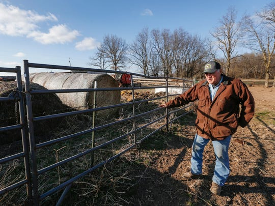 Bob Darrow points to a section of barbed wire that