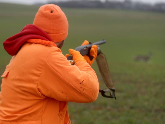 A hunter spots a deer while hunting during the opening
