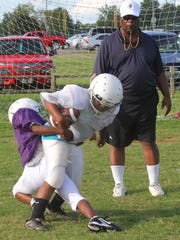 Coach Kenneth Clark watches two players on his team, the Jr. Pro Vikings, at practice. Clark has coached in the Murfreesboro Parks and Recreation Youth Football League for 37 years.