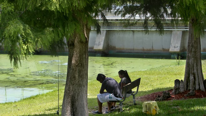 Luis Rodriguez and Atenas Morales fish near a green algae bloom  at the W. P. Franklin Lock & Dam in Olga Tuesday. The fish weren't biting.